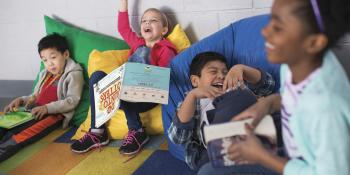 4 kids on bean bag chairs reading and laughing