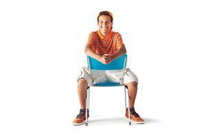 boy sitting backwards on blue chair