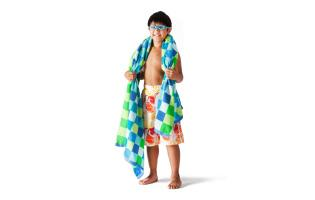 boy wearing bathing suit wearing goggles and towel