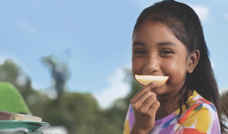 girl using apple slice as smile