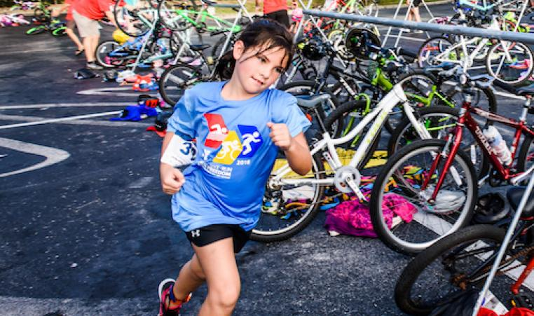 girl triathlon contestant running by bikes