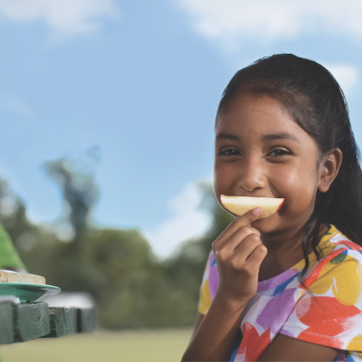 girl using apple slice as smile