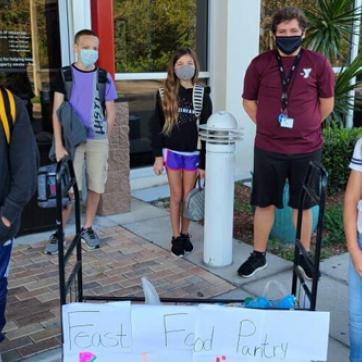 Middle school kids wearing masks collecting food