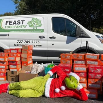 food distribution and the grinch laying on ground in front of boxes of food