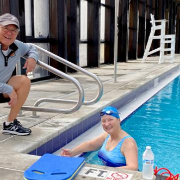 senior woman in pool smiling, with male coach squatting for photo