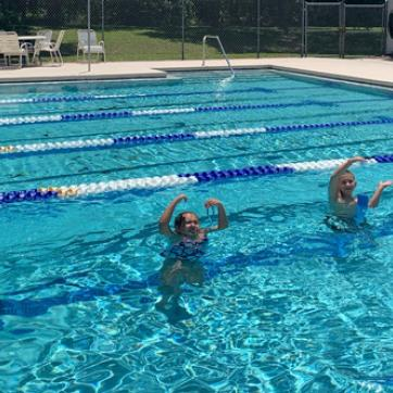 young swimmers in outdoor ymca pool making letters YMCA with arms